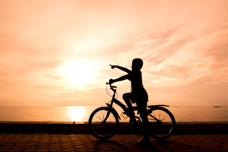 Biker family silhouette , family at the beach at sunset. photo