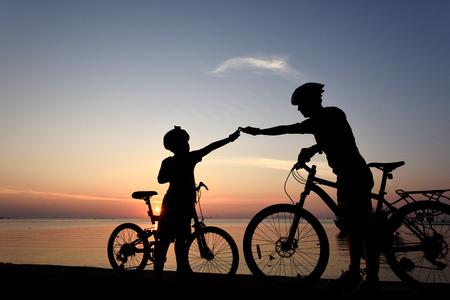 pa: Silhouette lovely family at sunset over the ocean, biker family.