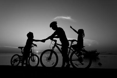 pa: Silhouette lovely family at sunset over the ocean, biker family. Black and white.