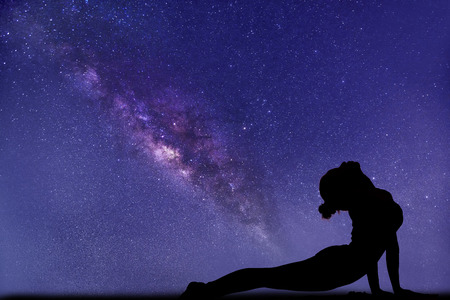 milky way, close up view. Professional woman yoga pose foreground.