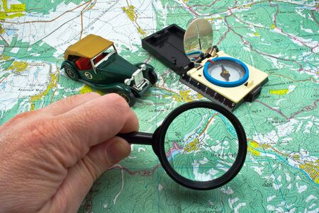 Compass and magnifying glass on a background a map