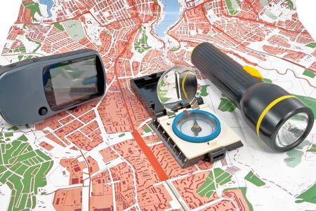 A handheld GPS, flashlight and compass unit sits on a topo map
