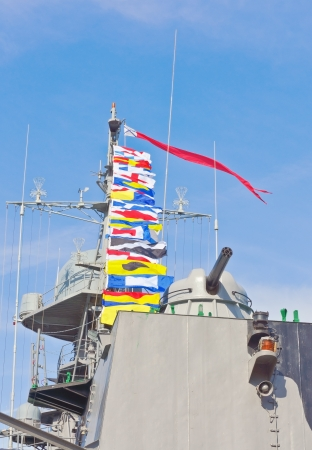 Nautical flags and cannon against blue sky photo