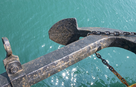 fastened: heavy black anchor fastened on a rope overwater  Stock Photo