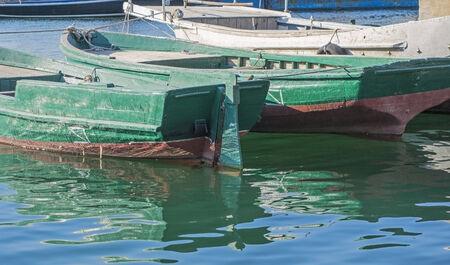 fishing boat full of water near a pier photo