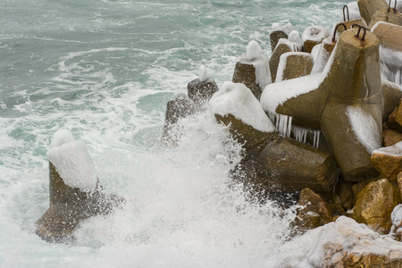 roaring sea: Breakwater covered by ice on a background a sea