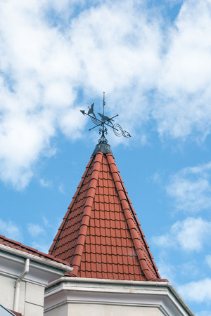 weather vane on roof and blue sky background photo