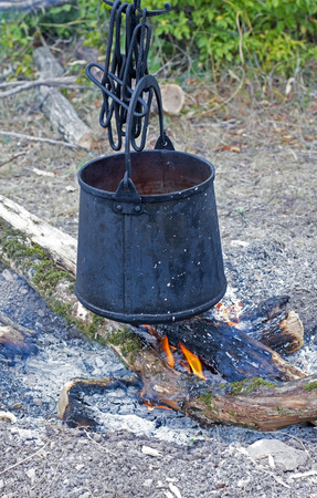 sooty: sooty bucket hanging on hooks over fire