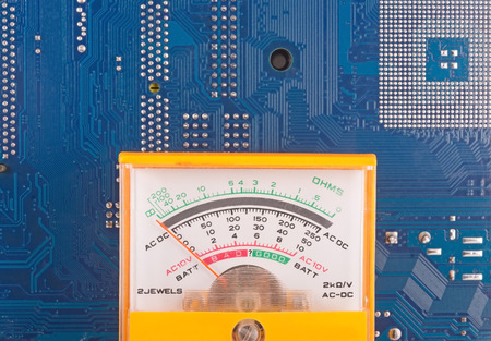 miniaturization: the yellow Analog tester on  background of electronic circuit board