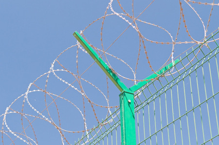 interdiction: fence with barbed wire  and blue sky Stock Photo