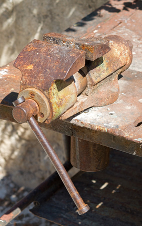 holdfast: old rusty vise on a metal table Stock Photo