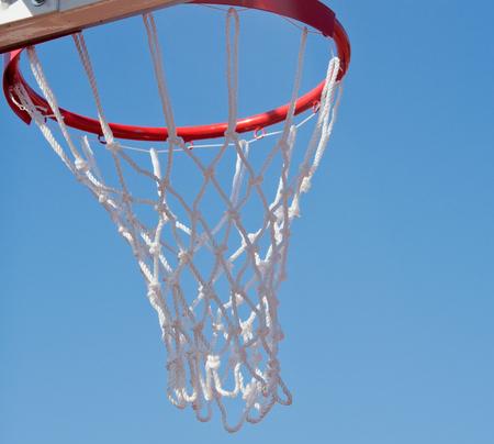 Red basketball hoop against a blue sky