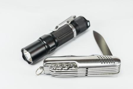 sitting on the ground: knife and led flashlight on a white background