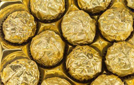 Candies wrapped in golden foil in box