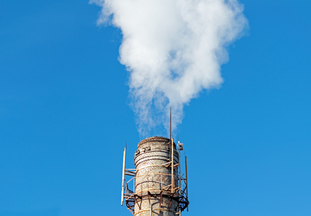 Smoke emission from factory pipe on a background of the blue sky Stock Photo