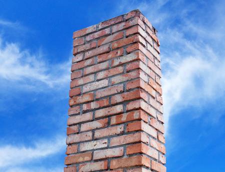 abandoned factory: brick smokestack isolated on background of blue sky