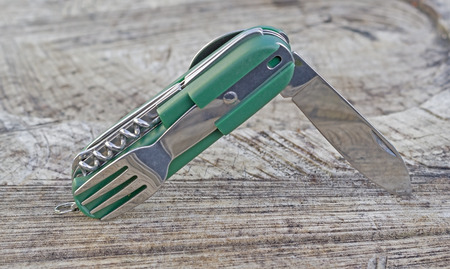 Multi tools knife on a wooden background