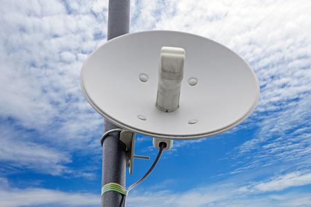 mała antena talerzowa na białym tle na tle nieba