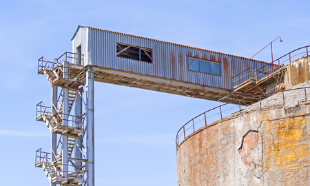 Old big industrial tank for the treatment of wastewater against the blue sky Stock Photo