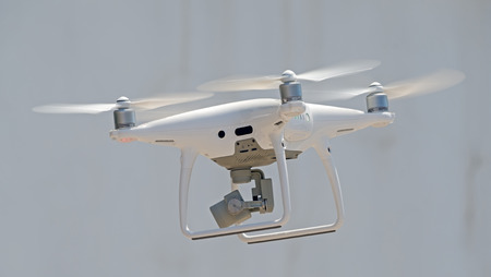 Flying drone quadcopter in front of white building