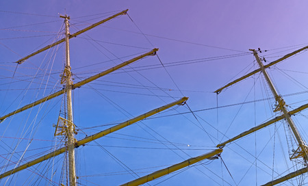Masts and rigging of a sailing ship against sky