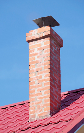 house from a red brick with a pipe on background sky 版權商用圖片
