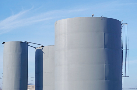 big industrial tank for the treatment of wastewater against the blue sky Stock Photo
