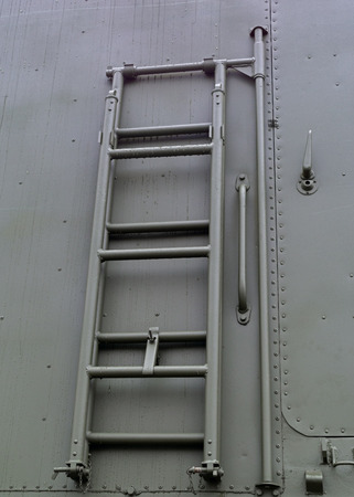Lifting metal ladder on Board military machine attached to the rear of the machine 免版税图像 - 121539629