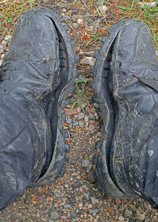 Old dirty mens boots. Old ripped shoes