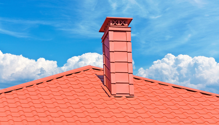 chimney on the roof of the house against the blue sky