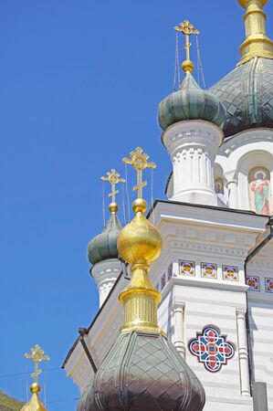 The dome of the Church with a cross against the blue sky Фото со стока - 124709517