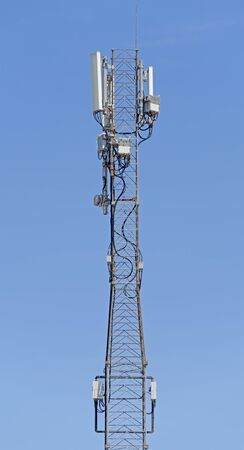 Tower with aerials of cellular on a background mountains and blue sky