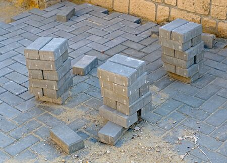 Laying gray concrete paving slabs, unfinished work on laying paving slabs