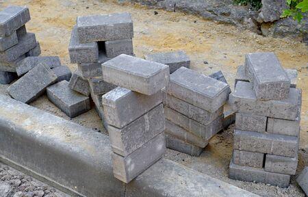 Układanie szarych betonowych płyt chodnikowych, niedokończone prace przy układaniu płyt chodnikowych