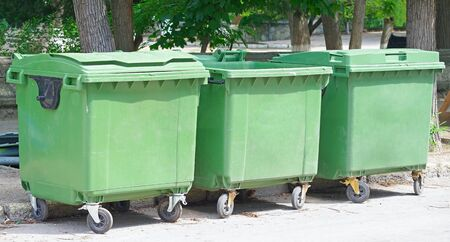 three green garbage containers in city parks