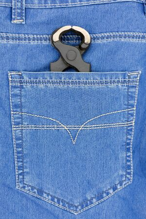 Black pincers in new blue jeans pocket
