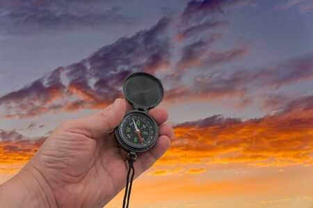 the hand with compass on background evening sky