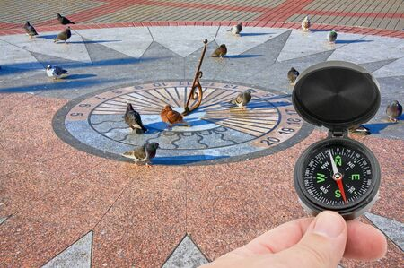 compass in hand on background sundial on granite base