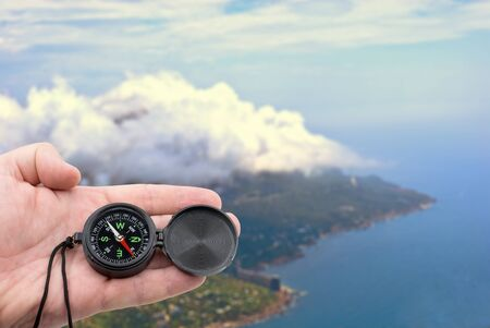 hand with compass on background of mountains