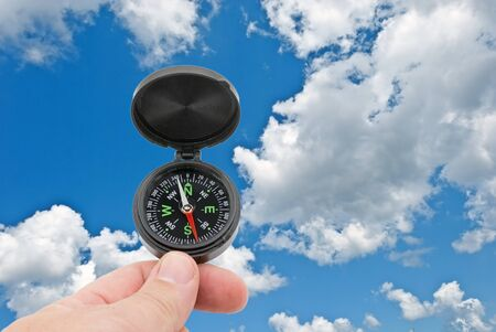 hand with compass on background blue sky