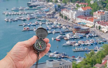 compass in hand on background Boats along the waterfront Standard-Bild - 133457130