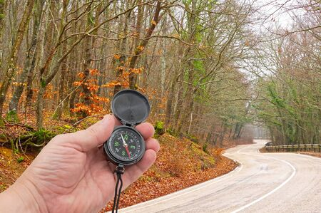compass in hand on background Mountain road Standard-Bild - 133457135