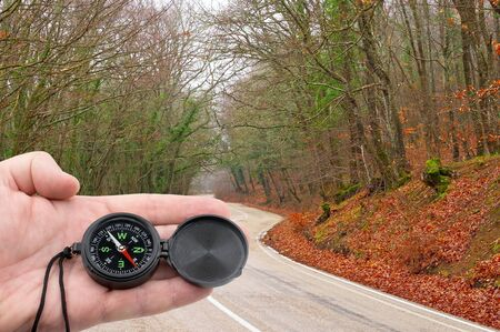 compass in hand on background Mountain road Standard-Bild - 133457137