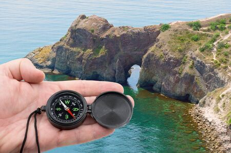 hand with compass on background of sea Standard-Bild - 133457140