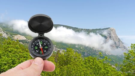 the hand with compass on background of mountains