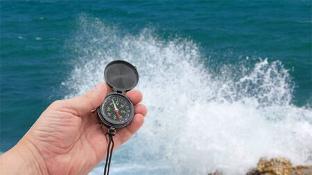 hand with compass on background of sea Standard-Bild - 133458038