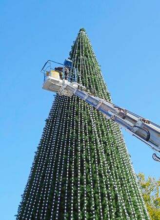 Worker on the crane install and decorate the Christmas tree Banco de Imagens