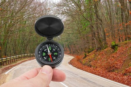 compass in hand on background Mountain road