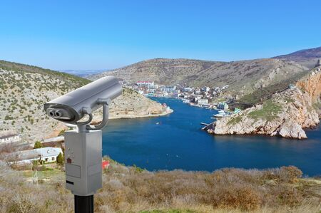 Coin-operated binoculars looking out over Mountains and the sea