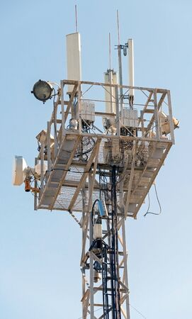 Tower with aerials of cellular on a background blue sky
